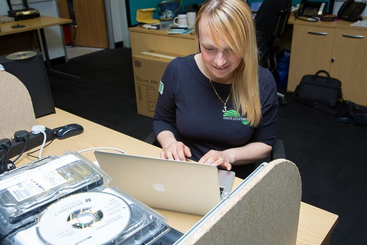Emerald Engineer working on MacBook to assist a customer with remote working